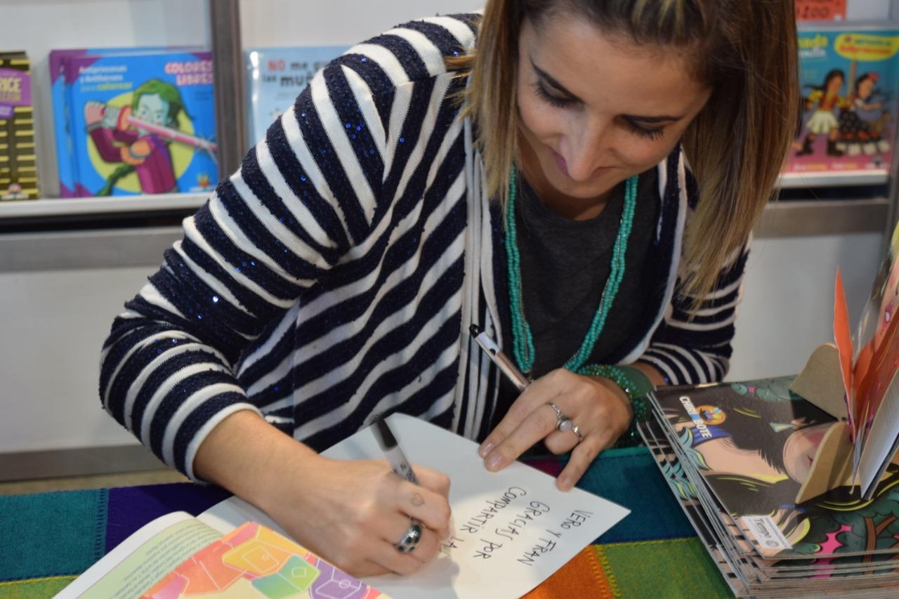 Ro Ferrer, ilustradora, firmando uno de sus libros.